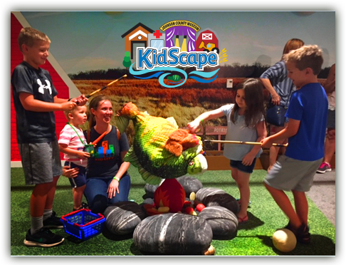 A group of kids pretending to fish in kidscape in the museum