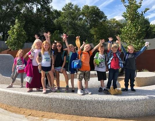 Kids in Museum Explorers program taking a group picture outside of building on public art piece
