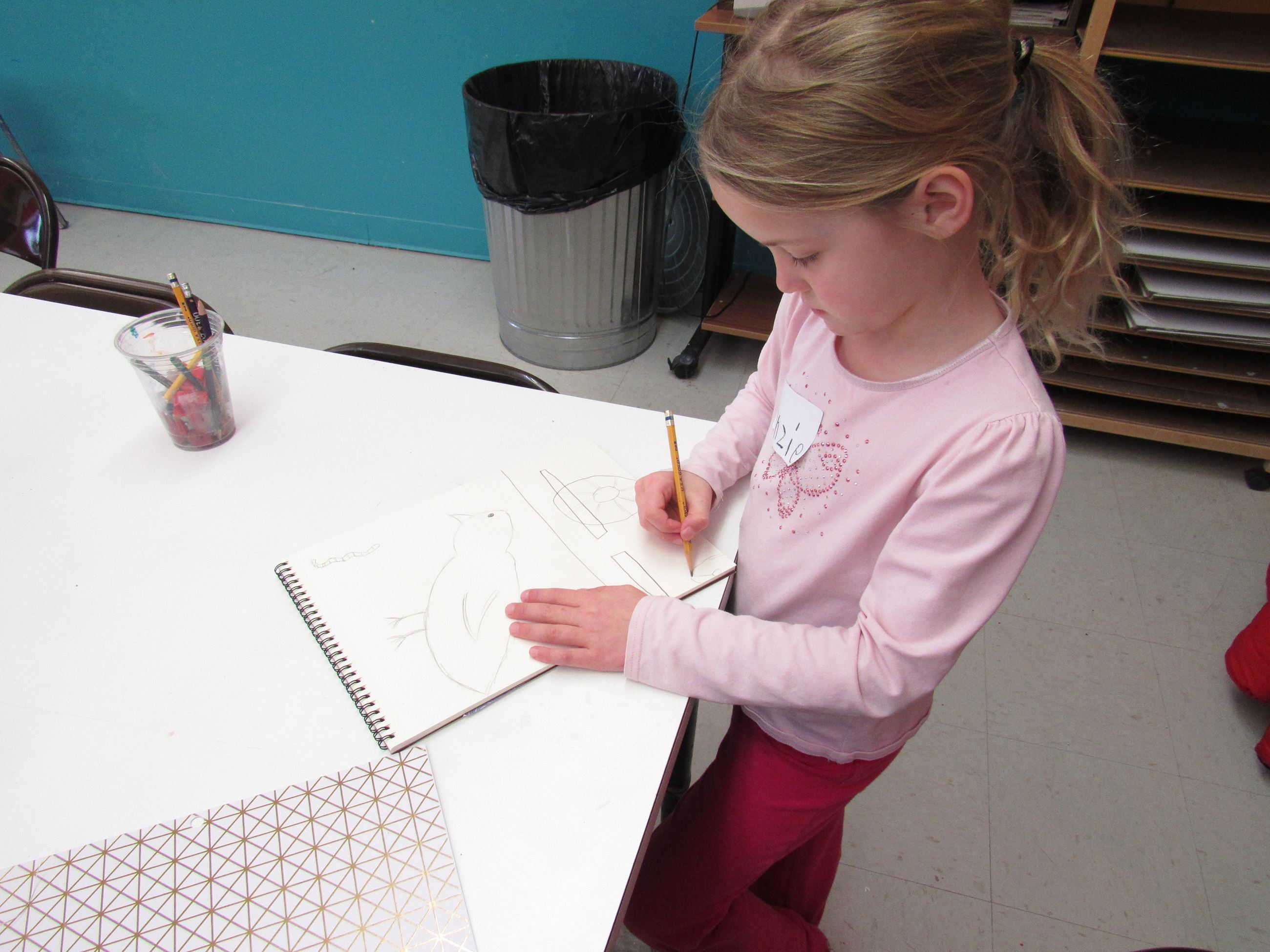 Young girl draws on paper Opens in new window
