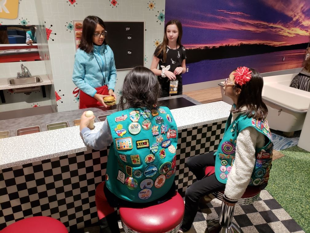 Four Girl Scouts interacting in the 1950s diner area of the museum's Kidscape exhiibt.
